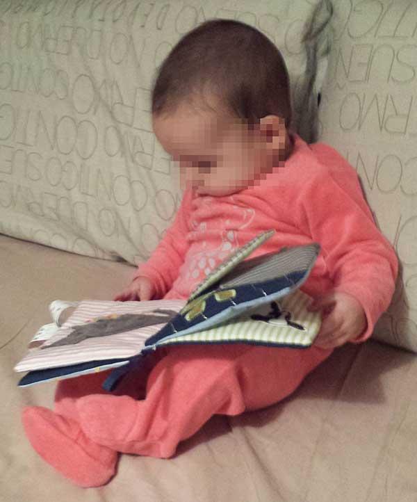 Bebé 5 meses con un libro de tela